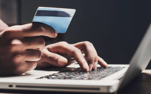 Hands on computer holding credit card