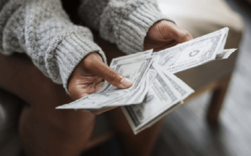 image of person holding money