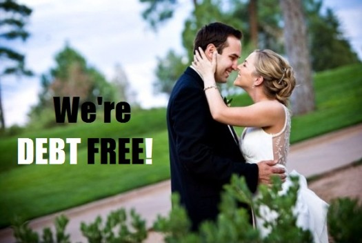 """Deacon and Kim Hayes in wedding attire with nature background and words, """"We're Debt Free!"""""""