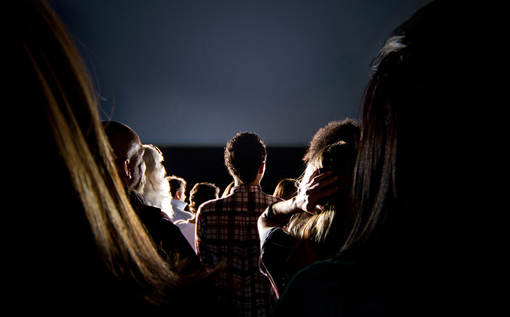 People Watching a Movie Outside at Night