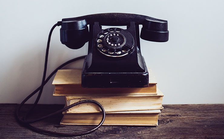 Black Rotary Phone On Top Of Books on Wooden Table