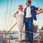 rich couple standing on a boat