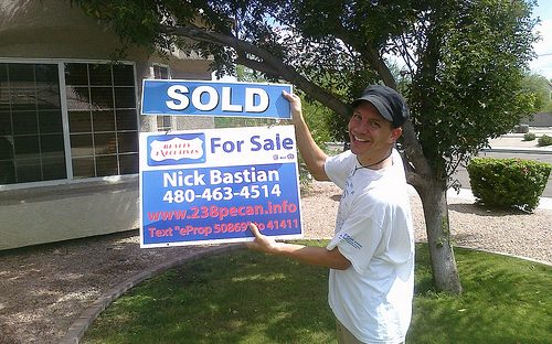 "Man in white t-shirt, tan cargo shorts, and black ball cap holding ""Sold"" and ""For Sale"" signs in front of a house"