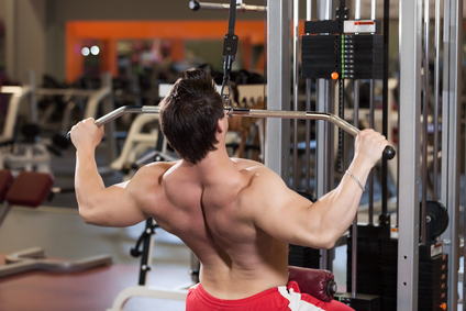 Man in red shorts lifting weights in a gym