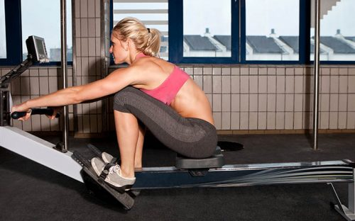 Woman rowing at gym