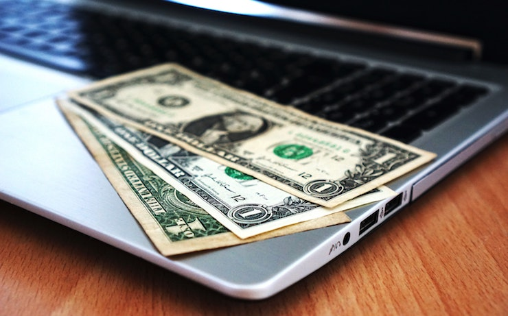 one dollar bills laying on a laptop computers