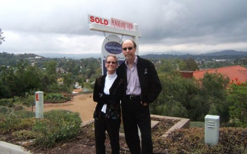 Couple Standing in font of Real Estate Sold Sign
