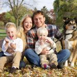 Family sitting on leaves in fall