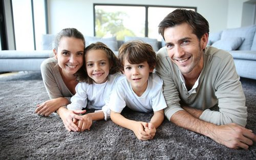 Family laying on gray carpet