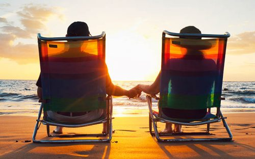 Couple Holding Hands on Lawn Chair at the Beach