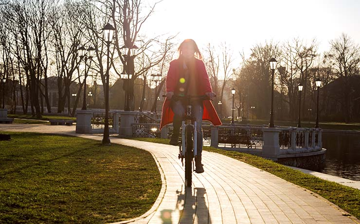 Woman Riding Bike in Park at Sunset