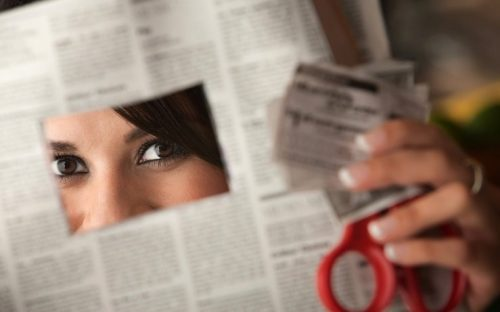 Lady cutting coupon out of newspaper