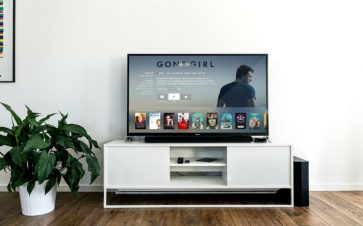 Sling TV ad on a flat screen TV sitting on a white cabinet beside a plant FI