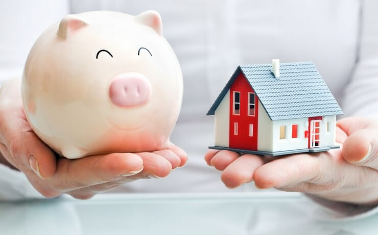 Person holding piggy bank and miniature house FI