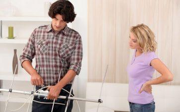 Man in plaid shirt and woman in pastel t-shirt assembling antenna FI