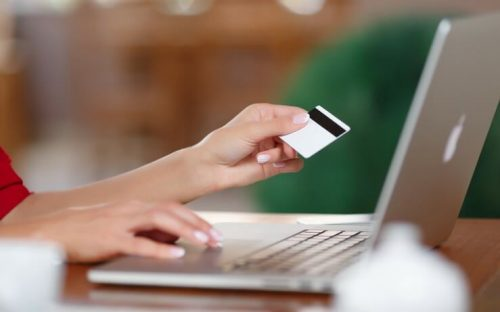 Woman holding credit card typing on laptop computer FI