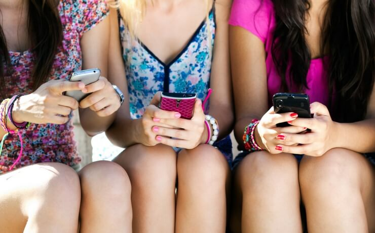 3 girls sitting down and holding cell phones FI