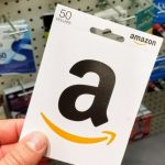Hand holding $50 Amazon gift card in front of gift card display FI