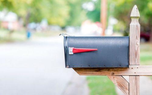 Black mailbox on wooden post FI
