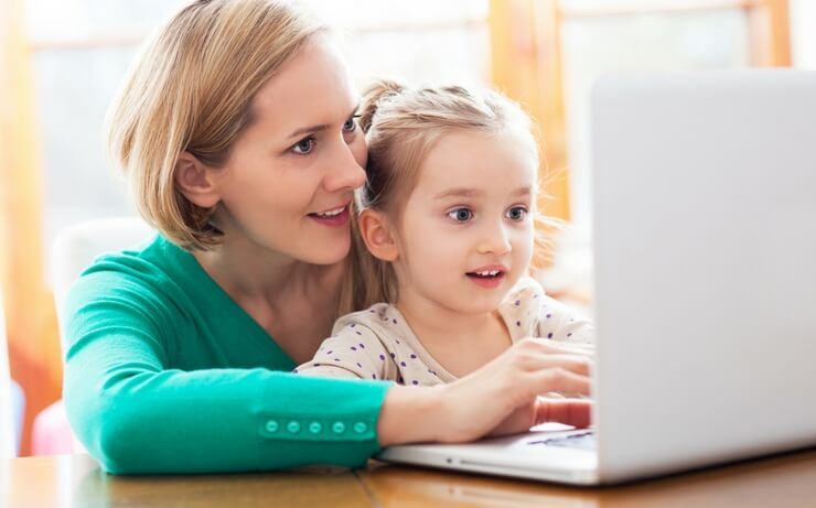 Lady with little girl working on computer FI