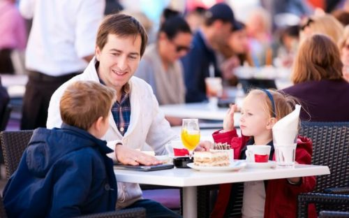 Man with a boy and girl eating in a restaurant FI