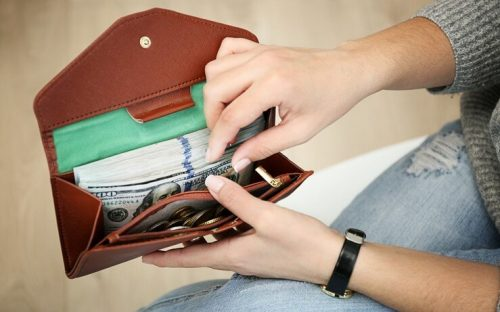 Woman holding open wallet with money in it FI