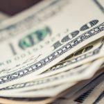 Close up photo of hundred dollar bills edges