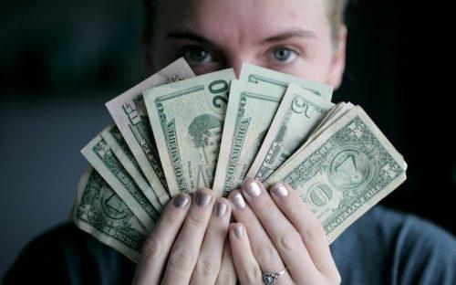 Woman looking over handful of money splayed in her hands