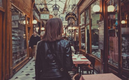 Woman walking down an alleyway shopping while wearing a leather jacket