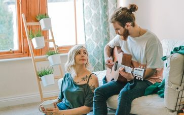 Couple sitting together at home while one plays the guitar