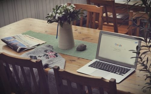 laptop sitting on a table next to sweater and pitcher of flowers