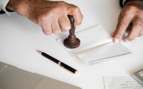 Man stamping a check with a notary stamp