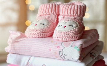 Pink booties sitting on top childrens clothes for babys