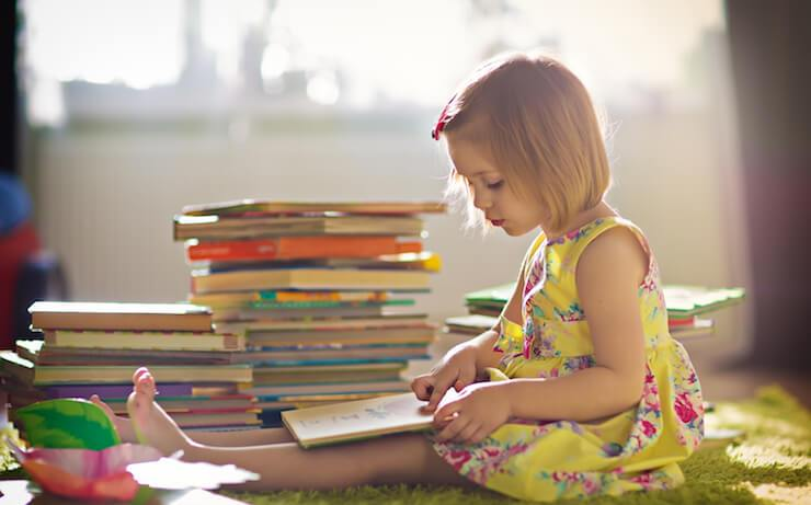 Little blond girl wearing yellow dress reading books next to a stack of books