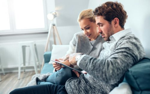 Couple looking into AARP on their tablet together