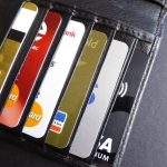 6 different credit cards in a black leather wallet laying on grey table