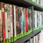 Wall of bookshelves filled with DVDs for sale