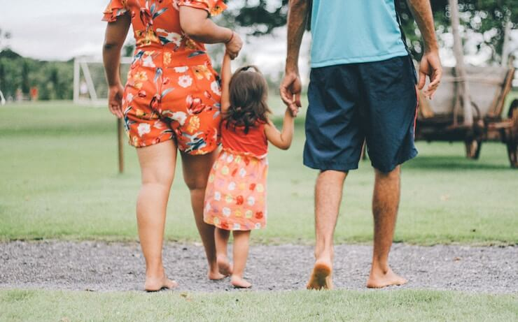 Family of 3 holding hands and walking on grass outside barefoot