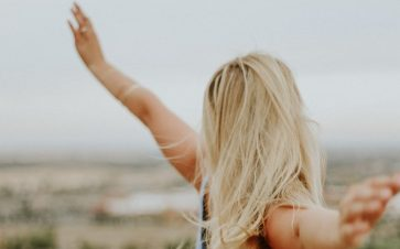 Blonde woman with her arms out in the air feeling free