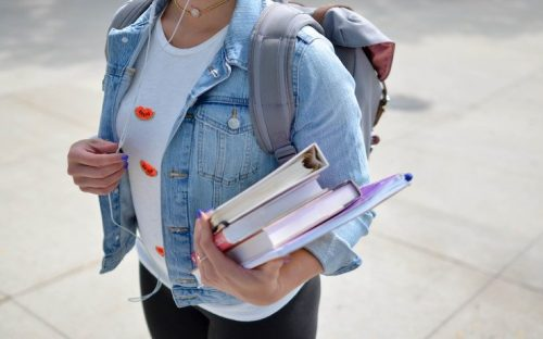 Girl wearing jean jacket while holding books, backpack and listening to music on headphones