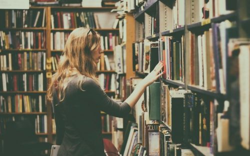 Woman looking at books at vintage bookstore