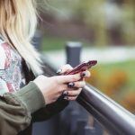 Woman with blond hair wearing green bomber jacket using her cell phone outside