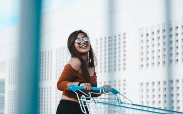 Girl with a big smile pushing a grocery cart