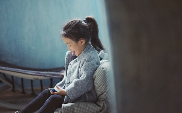 little girl learning and playing on her phone