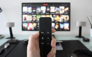 Person holding a TV streaming remote while picking out a show to watch