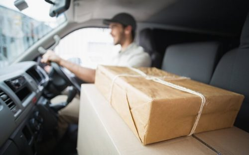 Man driving a car with packages in the passenger seat to be delivered