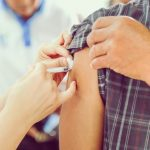 Person wearing grey plaid shirt getting a shot most likely a flu shot