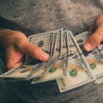 Man holding hundreds of dollars wearing a grey shirt