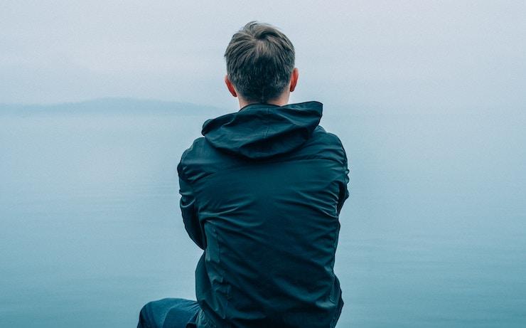 Orang yang melihat ke badan air sambil memikirkan apakah dia bisa pensiun