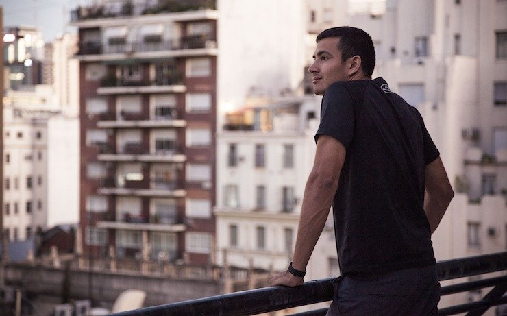 Man looking out to a city buildings full of apartments